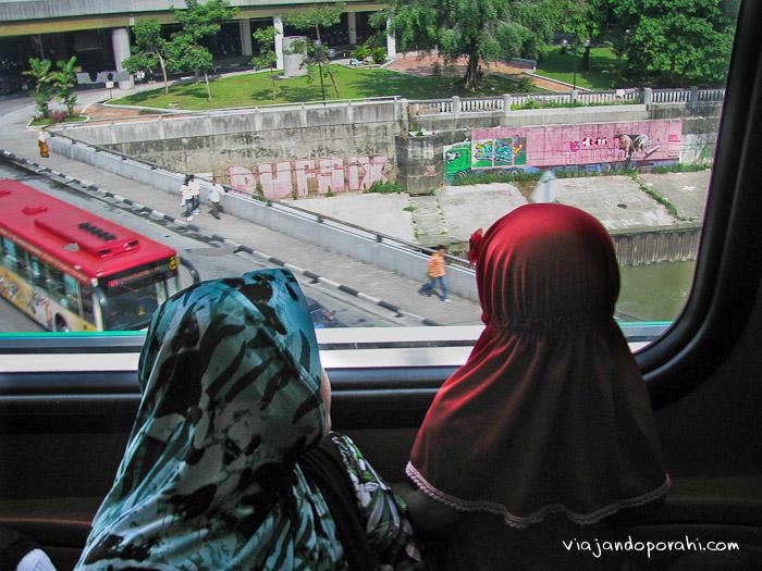 Madre e hija miran por la ventana del monorriel (la foto la saqué durante el día, claramente)