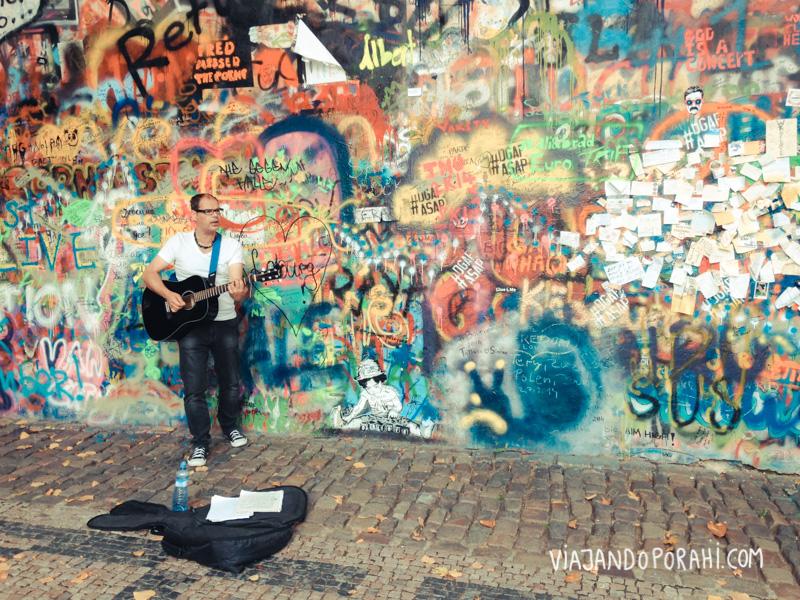 Músico callejero en Praga, frente al muro de John Lennon.